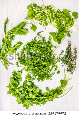 Bunches of Green herbs for salad : Lovage , borage eaves , garden cress,miner's lettuce , thyme ,coriander, parsley on white wooden background, top view - stock photo
