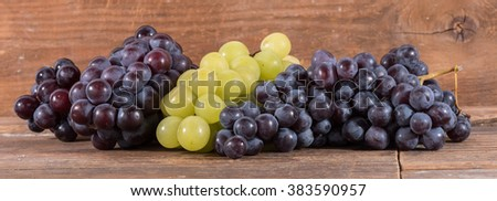 Bunches of white and black grapes, on wooden background - stock photo