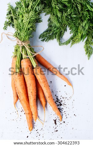 Bundle of carrots with soil over light blue wooden background. Top view - stock photo