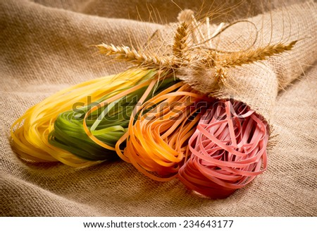Bundle of colorful uncooked pasta tagliatelle with spikelets on sackcloth - stock photo