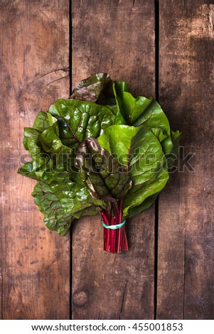 bundle of fresh and organic red chard leaves on a brown, rustic wood background with copy space, close up and vertical - stock photo