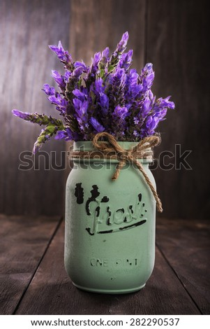 bundle of lavender flowers in retro vase isolated on an old wooden background - stock photo