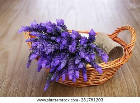 bundle of lavender flowers in wicker basket on vintage wooden table - stock photo