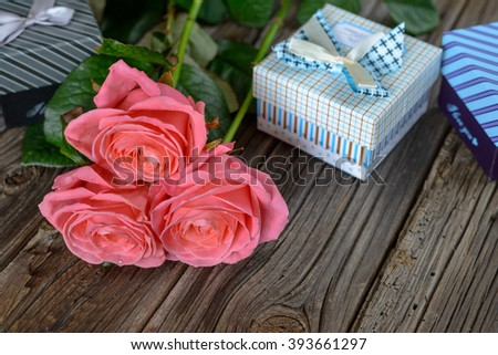 Bundle of three beautiful pink stemmed roses and little gift boxes on old wooden table for Valentines Day concept - stock photo