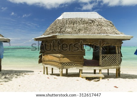 bungalow on the beach with crystal blue ocean - stock photo