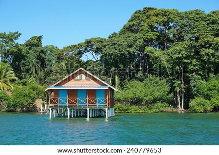 Bungalow over the sea with tropical vegetation in background, Caribbean, Bocas del Toro, Panama - stock photo
