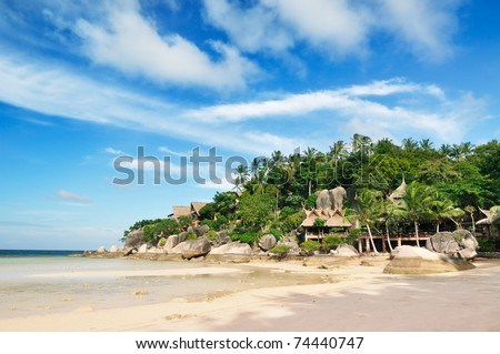 Bungalows under the palms on the beach - stock photo