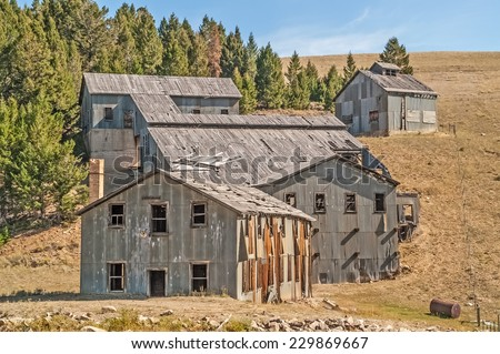 Bunkhouse, flotation mill, and other buildings sit abandoned in a Montana ghost town - stock photo