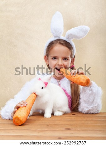 Bunnies eating large carrots - little girl with bunny ears feeding her white rabbit - shallow depth of field - stock photo