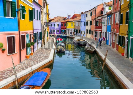 Burano canal full of boats and colorful houses. - stock photo