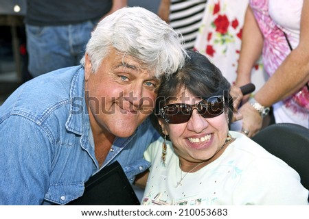 BURBANK/CALIFORNIA - JULY 26, 2014: Jay Leno former host of the Tonight Show poses for a picture with a fan at the Burbank Car Classic July 26, 2014, Burbank, California USA  - stock photo