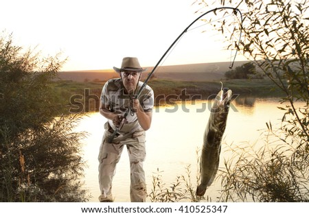 Burbot. Man fishing  in the river at sunset - stock photo