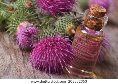 burdock oil in a glass bottle on a background of flowers. macro horizontal  - stock photo