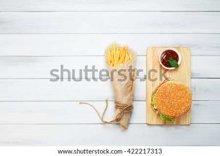 Burger and Chips. Hamburger and french fries wrapped in brown wrapping paper. Fast food take away at white shabby chic wood. Hamburger with tomato sauce. Top view, flat lay with copyspace - stock photo