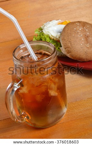 burger and iced tea on wooden board - stock photo
