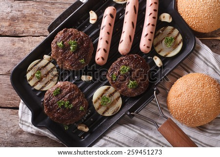 Burger and sausages on a grill pan. horizontal view from above close up