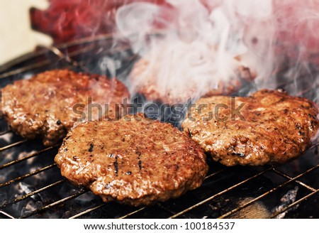 Burger patties on a grill (selective focus) - stock photo