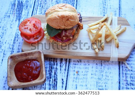 burger tomato cheddar cheese french fries red onion ketchup in wooden bowl on a cutting board on a wooden background/hamburger fries ketchup/horizontal straight burger and fries - stock photo