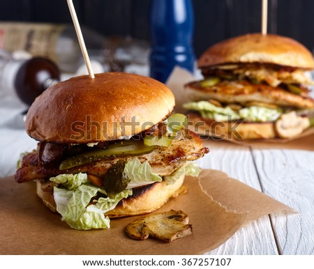 Burger with chicken, cheese sauce and mushrooms - stock photo