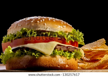 Burger with chips focus on front  in black background. - stock photo