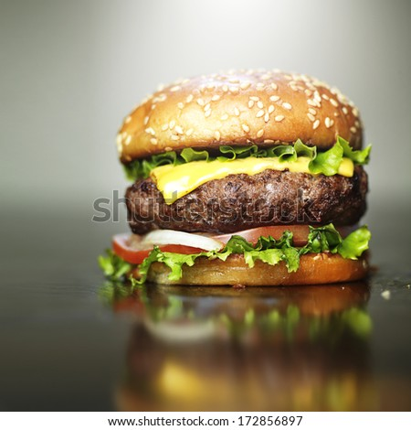 burger with melted cheese and sesame bun - stock photo