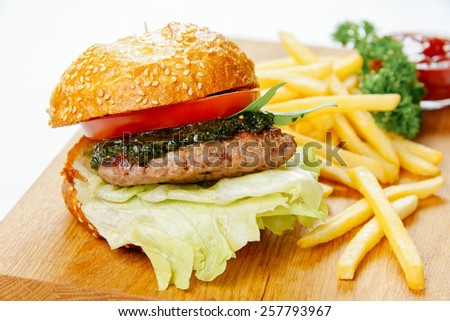 Burger with pesto sauce and french fries on a wooden stand - stock photo