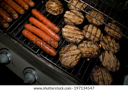 Burgers and hot dogs cook on the grill. - stock photo