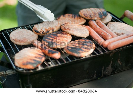 Burgers and Hot dogs on a Portable BBQ - stock photo