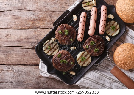 Burgers and sausages on a grill pan. horizontal view from above  - stock photo