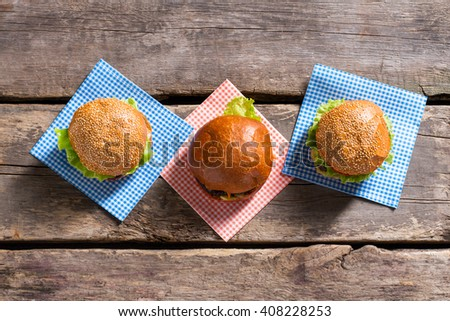 Burgers on checkered napkins. Top view of fresh hamburgers. Tasty food on wooden table. Fast food cafe's typical meal. - stock photo