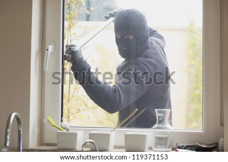 Burglar breaking a kitchen window with a crobar from outside - stock photo
