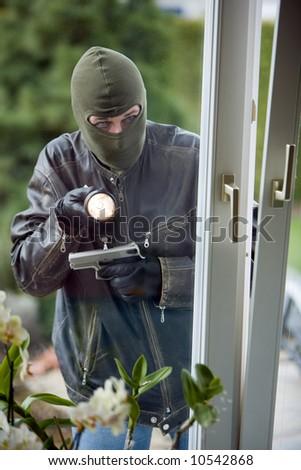 Burglar breaks into a residential building. - stock photo