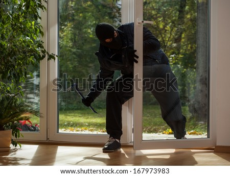 Burglar entering to house trough balcony window - stock photo
