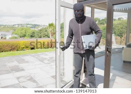 Burglar holding laptop and leaving home - stock photo