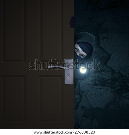 Burglar sneaking in a open house door during a break and enter past security locks and alarms, - stock photo