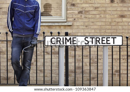 Burglar standing on street with crowbar and leather gloves next to crime street road sign - stock photo
