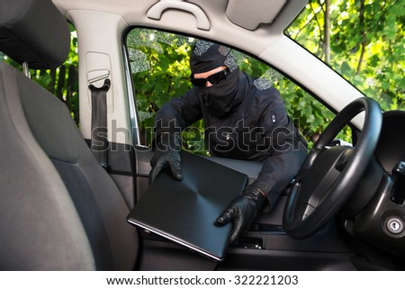 Burglar stealing laptop from a car whose windows he broke forcefully. - stock photo