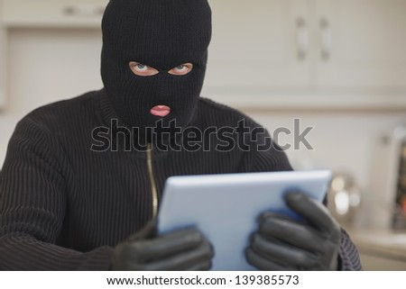 Burglar stealing the tablet pc in kitchen - stock photo