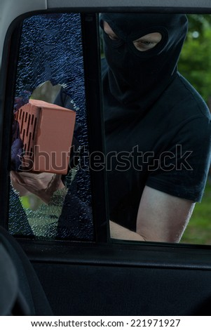Burglar use brick to smash car window - stock photo