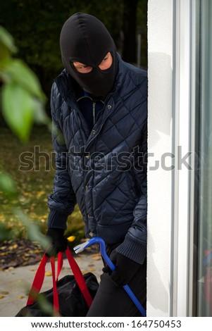 Burglar wearing mask with crowbar and bag - stock photo