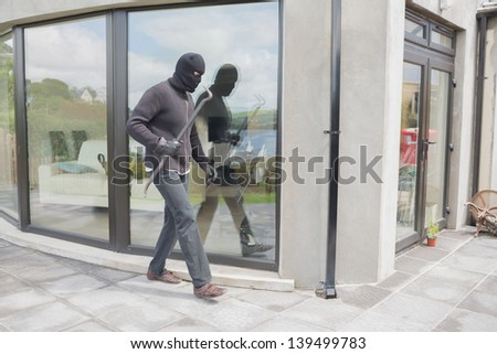 Burglar with cro bar outside home - stock photo