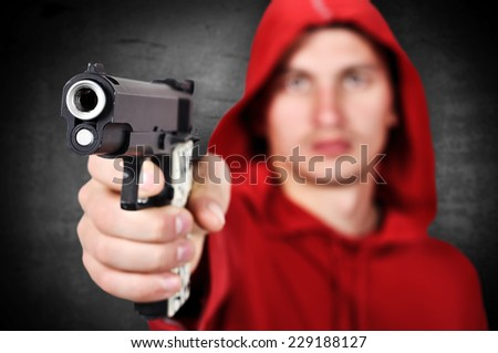 burglar with gun in hand on a black background - stock photo
