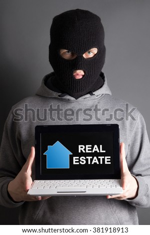 burglary and home safety concept -masked man holding computer with real estate site - stock photo