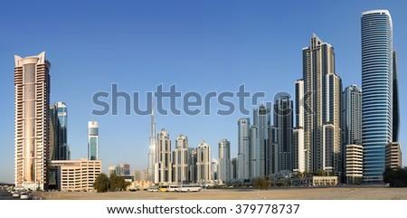 Burj Khalifa in Dubai among other skyscrapers. Panorama of residential district in Dubai, UAE with Burj Khalifa in distance - stock photo
