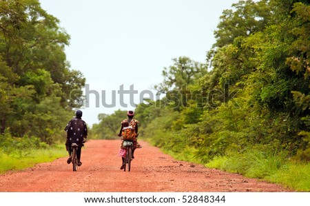 BURKINA FASO - AUGUST 11: Male and female African cycling, the bicycle is the popular means of transport, August 11, 2009 in Tiebele, Burkina Faso - stock photo