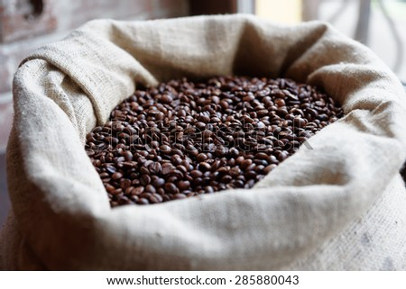Burlap sack of roasted coffee beans, shallow focus - stock photo