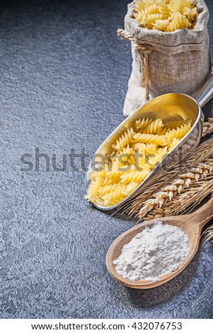 Burlap sack raw pasta serving scoop wooden spoon flour wheat rye ears on black background. - stock photo
