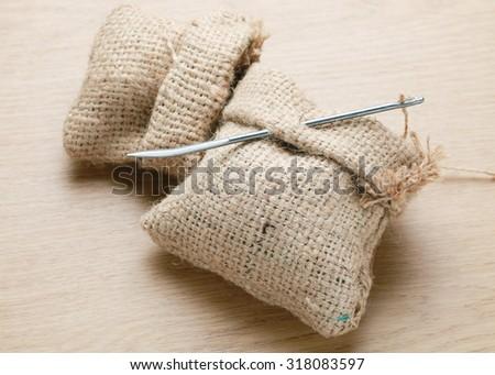 Burlap sack with Needle sewing sack on wood background. - stock photo