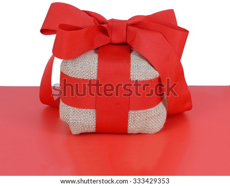 Burlap wrapped package tied up with a bright red ribbon on a red table with a white background. Could be Christmas or Valentine's Day present. Copy space below and room to create copy space above - stock photo
