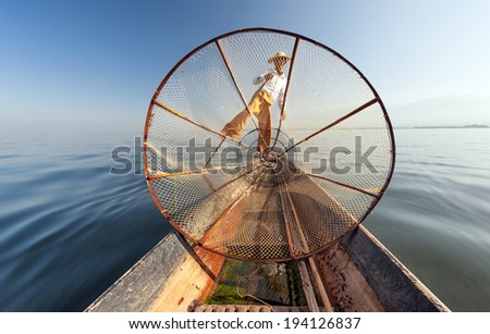 Burma Myanmar Inle lake fisherman on boat catching fish by traditional net. Outdoor photography - stock photo
